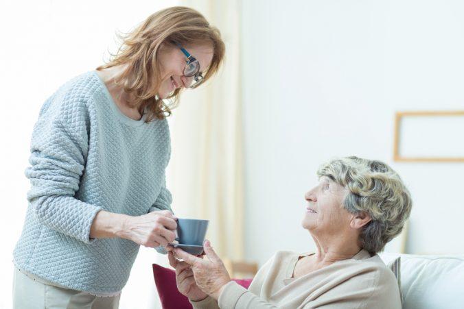 Äldre kvinna får kaffe av hemtjänstpersonal